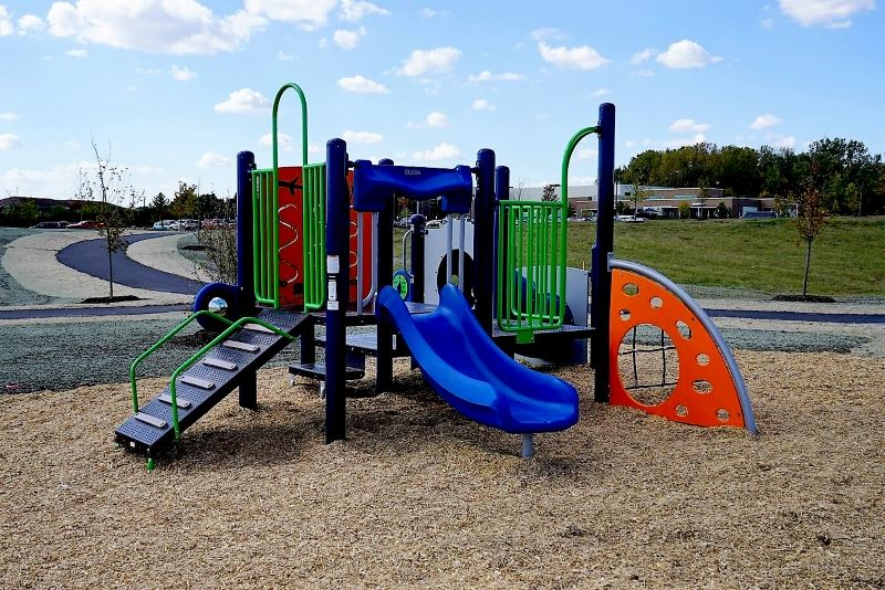 Playground equipment - blue slide, green railings, orange sail